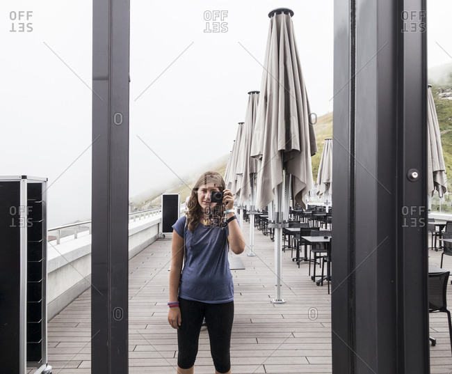 Teenage girl taking pictures with camera on restaurant patio