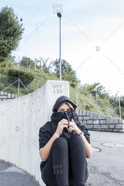 Shy teenage girl sitting on the ground alone