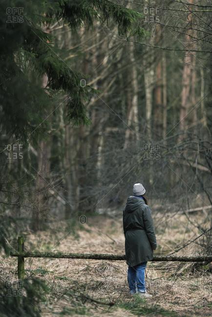 Woman in woolen cap standing in winter forest, rear view