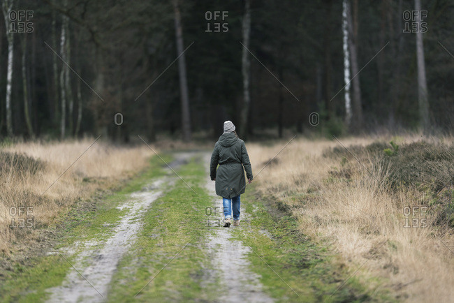 Woman in woolen cap hiking on dirt road in nature reserve, rear view