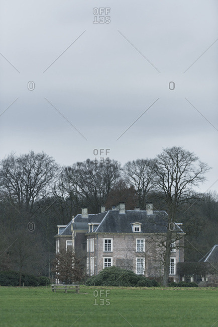 Country manor house between bare winter trees on overcast day