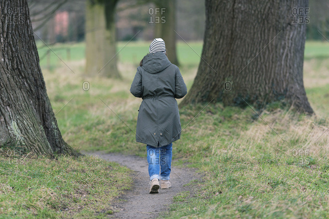 Woman hiking on pathway between big old tree trunks