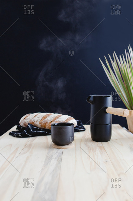 Steaming hot beverage served with freshly baked loaf of bread
