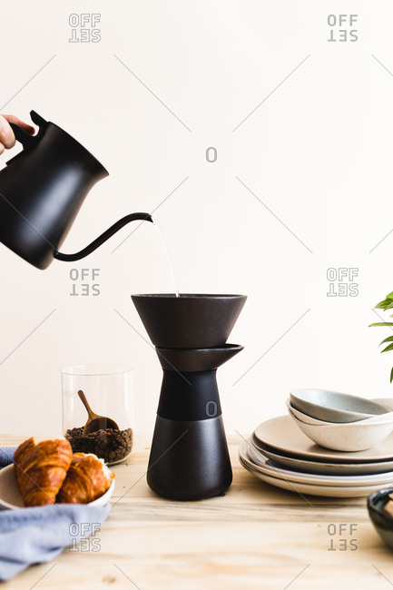 Person pouring hot water into a cone coffee maker