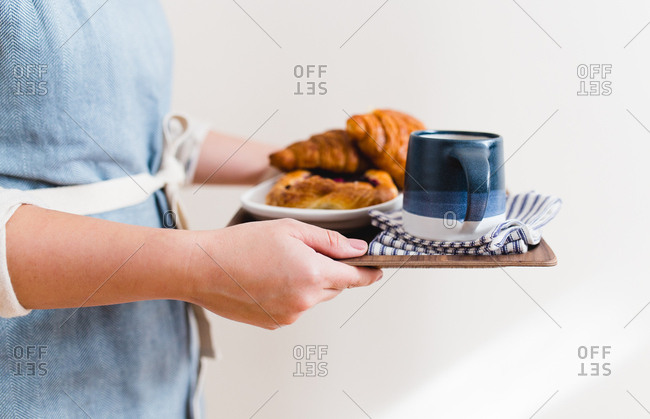 Person carrying a serving tray with croissants and a mug