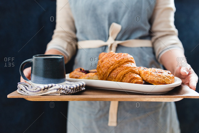 Person holding a serving tray with croissants, pastries, and a mug