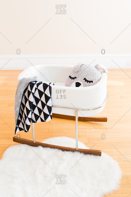 Baby cradle with knit blankets and stuffed animal