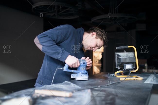 Man sanding counter on a job site