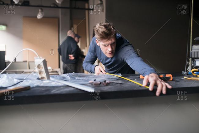 Man measuring countertop on a construction site