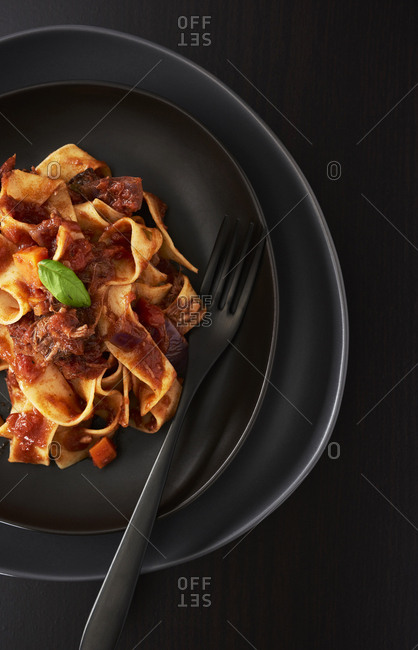Classic beef ragu with pappardelle pasta on black plate
