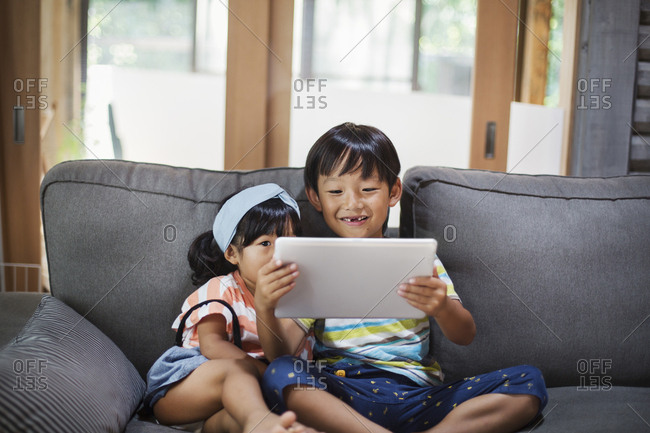 Boy and young girl with black hair sitting on a grey sofa, looking at digital tablet