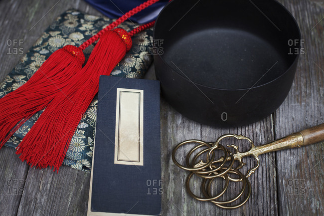 High angle close up of Buddhist prayer text, red silk tassel of a mala and black singing bowl