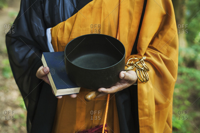 Close up of Buddhist monk wearing black and yellow robe, standing outdoors, holding prayer book and singing bowl
