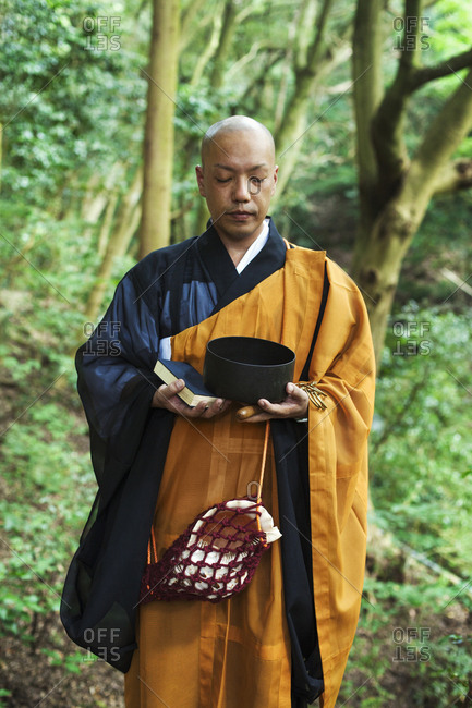 Buddhist monk with shaved head wearing black and yellow robe, standing outdoors, holding prayer book and singing bowl