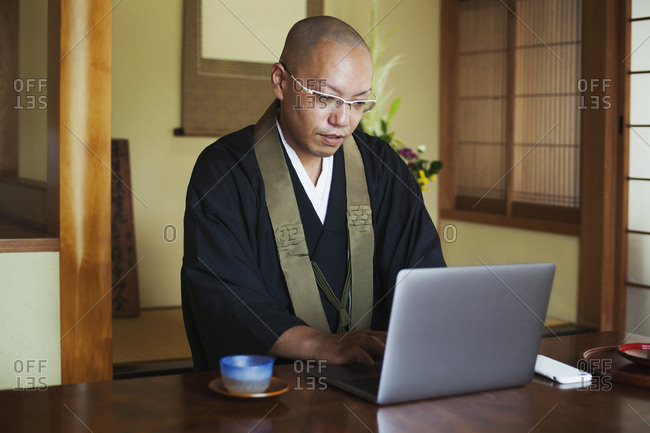 Buddhist monk with shaved head wearing black robe sitting indoors at a table, using laptop computer
