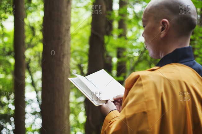 Side view of Buddhist monk with shaved head wearing black and yellow robe, standing outdoors, holding prayer text