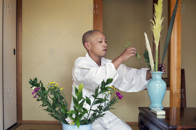 Buddhist monk with shaved head wearing white robe kneeling on floor, arranging flowers in blue vase