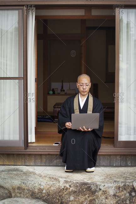 Buddhist monk with shaved head wearing black robe sitting outside temple, looking at laptop computer