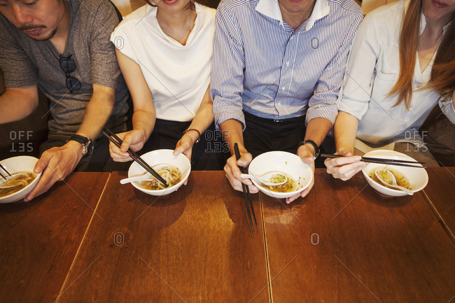High angle close up of four people sitting side by side at a table in a restaurant, eating from bowls using chopsticks