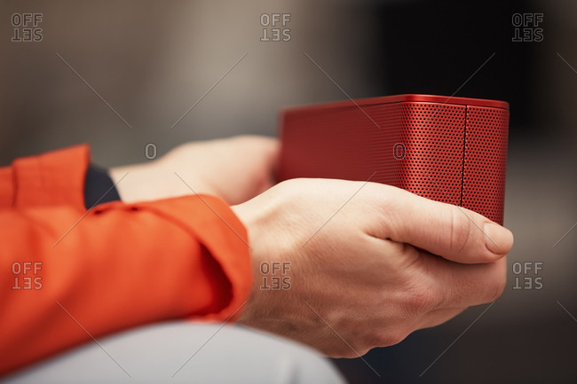 Woman holding portable wireless speaker and listening music