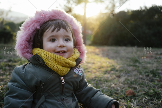 Portrait of happy toddler in winter by sunset