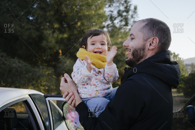 Portrait of happy baby girl on her father's arms