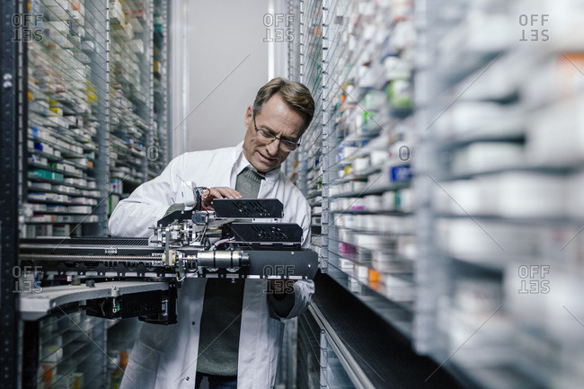 Pharmacist examining commissioning machine in pharmacy