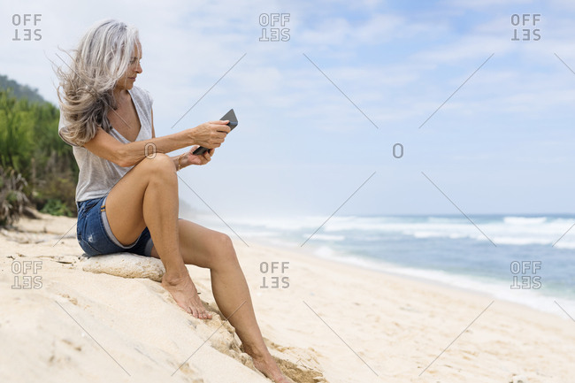 Beautiful smiling senior woman sitting at the beach- holding e-book