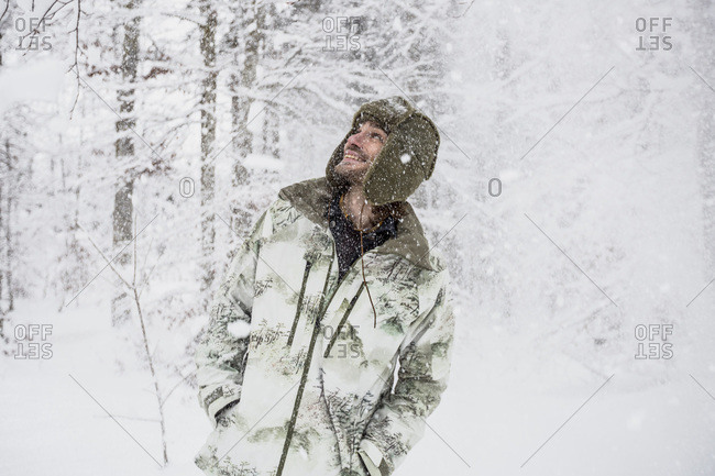 Happy man in camouflage jacket in winter forest