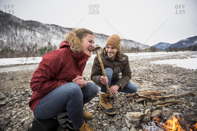 Happy couple on a trip in winter eating a sausage at camp fire