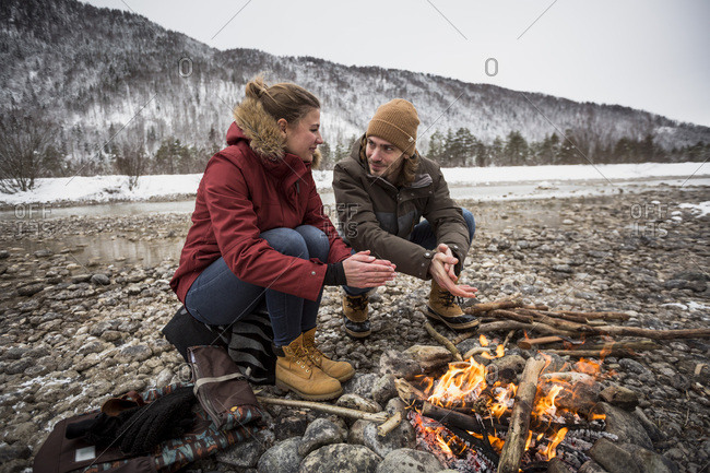 Couple on a trip in winter warming hands at camp fire