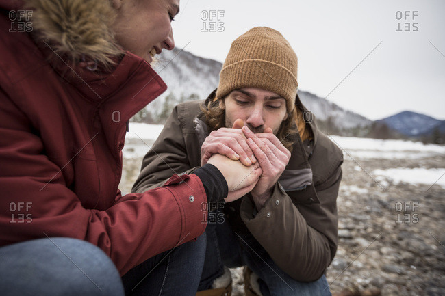 Couple on a trip in winter with man warming hands of woman