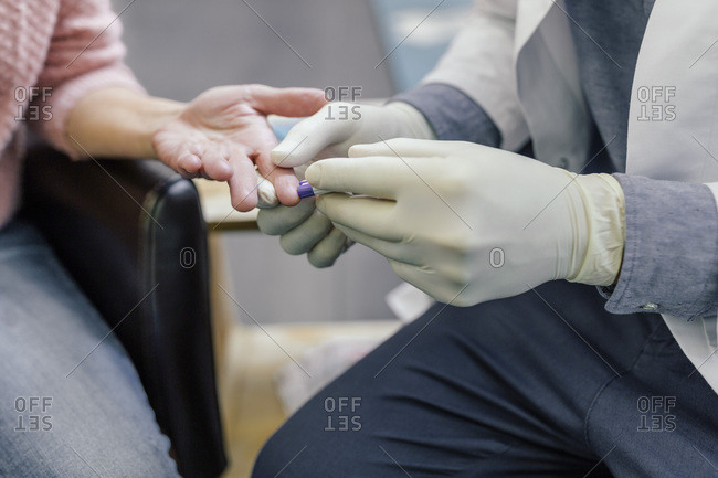 Pharmacist measuring blood sugar of customer in pharmacy