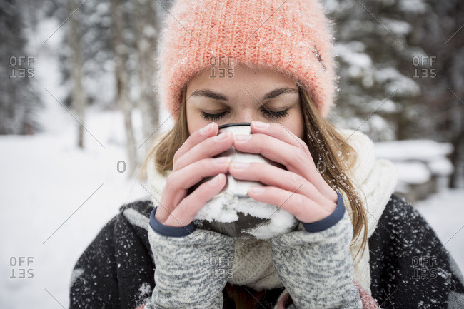 Young woman enjoying hot drink outdoors in winter