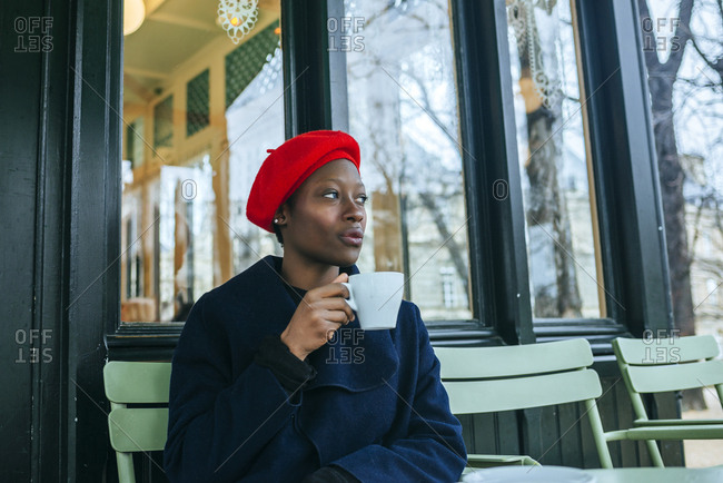 Young woman with parisian hat drinking coffee on paris bar terrace