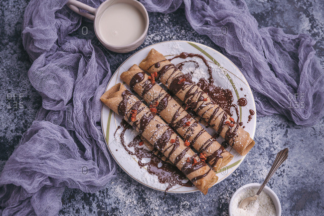 Spelt crepes with dark chocolate drizzle served on a plate