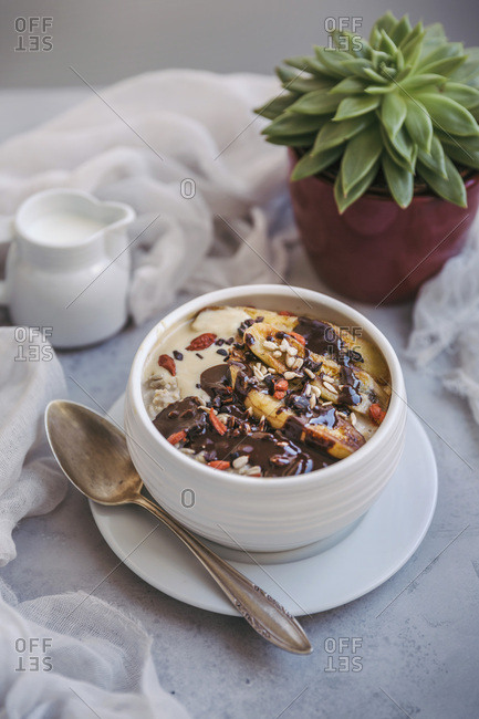 Bowl of porridge topped with caramelized bananas, melted chocolate, cacao nibs, goji berries and sunflower seeds