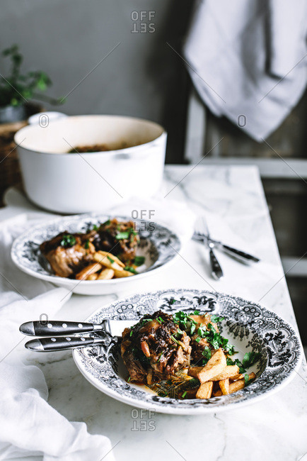 Oxtail casserole and chips on a rustic kitchen table