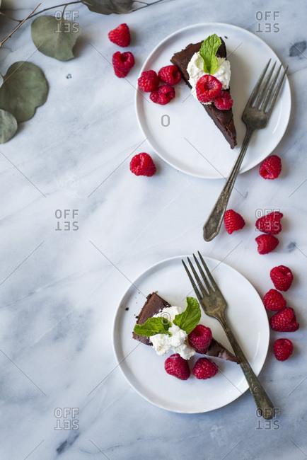 Dark chocolate cake with fresh whipped cream, fresh berries on white plates