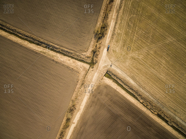 Aerial view of a car parked on a straight empty road in the middle of farmland in Estonia