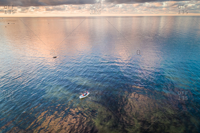 Aerial view of two people in a small wooden boat in the colorful baltic sea at sunset