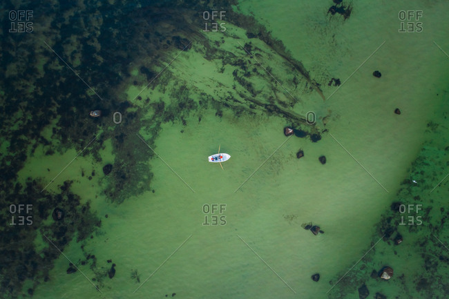Aerial view of two people fishing in a small wooden boat in the middle of the green baltic sea in Estonia