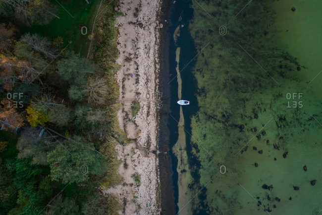 Aerial view of a boat moored in the greenish baltic sea close to the beach and forest in Estonia