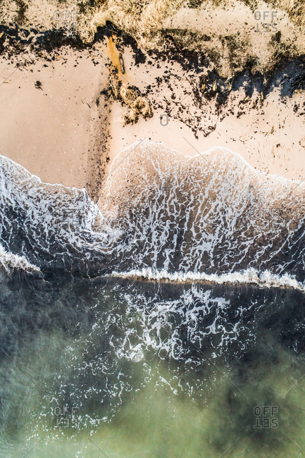 Aerial view of the baltic sea crashing on the black sand of the beach in Estonia