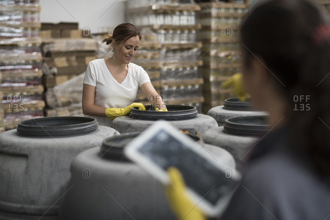 Woman looking tablet in olives warehouse factory controlling fruits fermentation