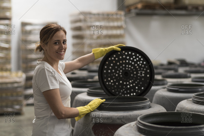 Woman looking at camera and smiling in olives fermentation factory