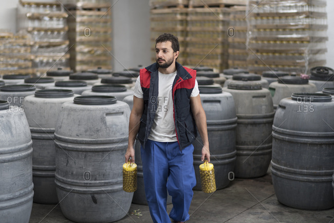 Man with bottles full of fermented green olives walking in factory