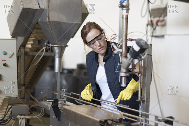 Worker woman revises machine in factory with protective glasses and gloves