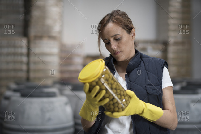 Woman looking olives bottle quality in food factory with barrels background