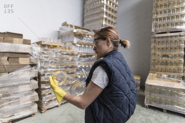 Woman looking plastic bottle in olives warehouse